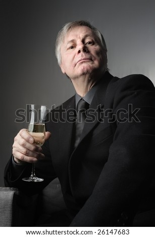 portrait of a senior businessman with a glass of wine