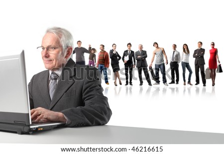 Portrait of a senior businessman working on a laptop with some people on the background - stock photo