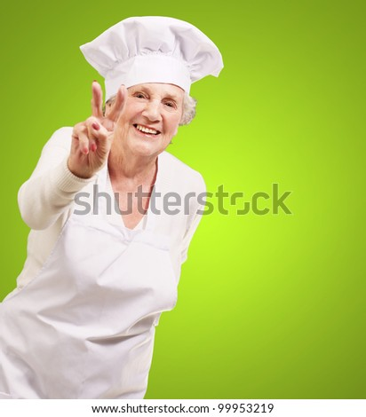 portrait of a senior cook woman doing an approval gesture over a green background