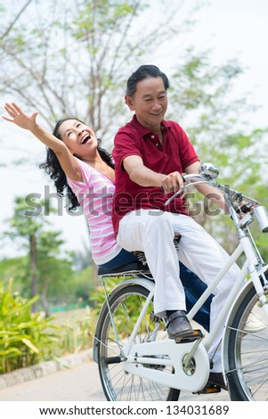 Portrait of a senior couple bicycling in the park - stock photo