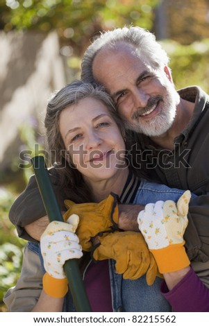 Portrait of a senior couple doing yard work - stock photo