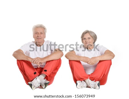 Portrait Of A Senior Couple Exercising On the floor of a gym on White Background - stock photo