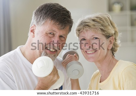 Portrait of a senior couple exercising with hand weights and smiling - stock photo