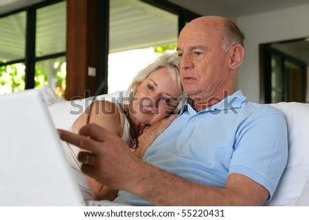 Portrait of a senior couple in front of a laptop computer - stock photo