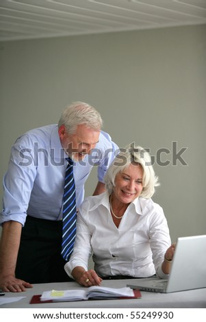 Portrait of a senior couple in suit in front of a laptop computer