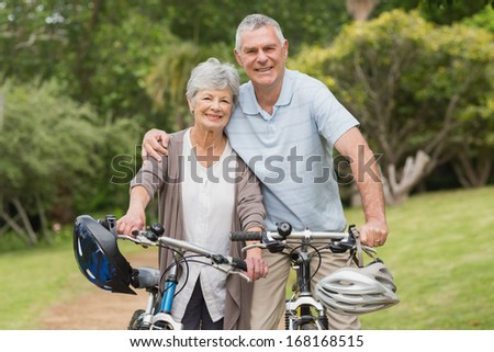Portrait of a senior couple on cycle ride at the park - stock photo