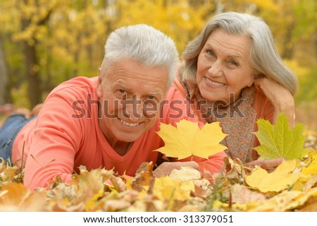 Portrait of a senior couple resting at autumn park - stock photo