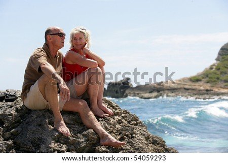 Portrait of a senior couple sitting on a rock - stock photo