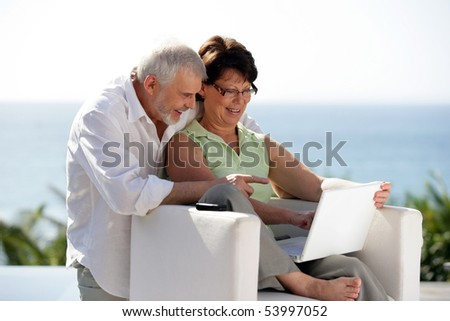 Portrait of a senior couple smiling in front of a laptop - stock photo