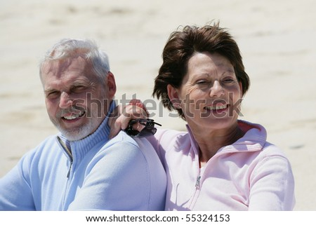 Portrait of a senior couple smiling sitting on the beach
