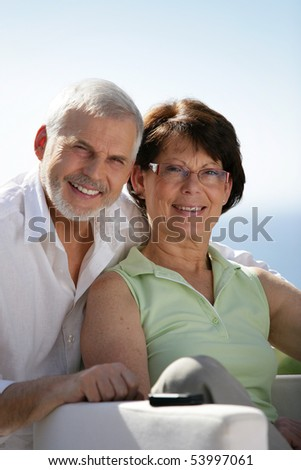 Portrait of a senior couple smiling with a laptop - stock photo