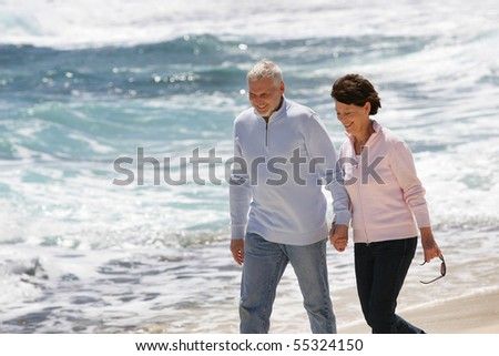 Portrait of a senior couple walking by the seaside - stock photo