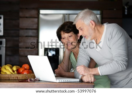 Portrait of a senior couple with a laptop computer - stock photo
