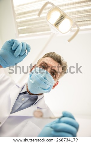 Portrait of a senior dentistin in mask in dental clinic.