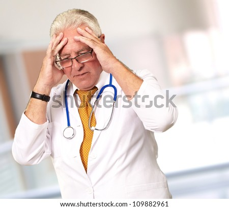 Portrait Of A Senior Doctor Holding His Head, Background - stock photo