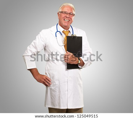 Portrait Of A Senior Doctor On Gray Background - stock photo