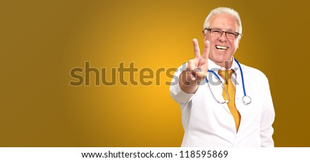 Portrait Of A Senior Doctor On Yellow Background - stock photo