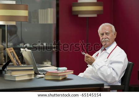 Portrait of a senior doctor working in his studio - stock photo