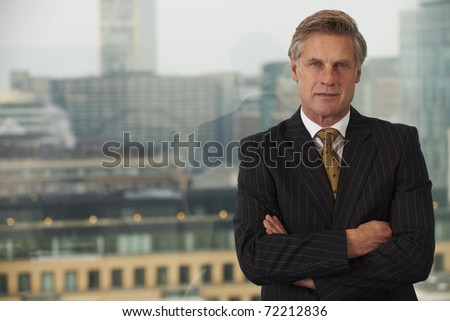 Portrait of a senior executive by a window smiling looking at camera with space for copy
