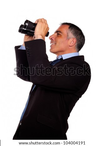 Portrait of a senior executive looking up through binoculars on black suit against white background