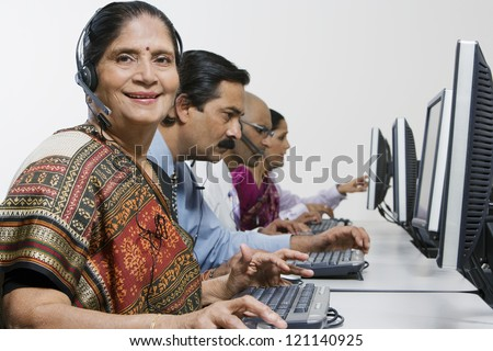 Portrait of a senior female customer service operator in sari with colleagues at office - stock photo