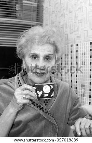 Portrait of a senior female having tea or coffee in her kitchen, in black and white