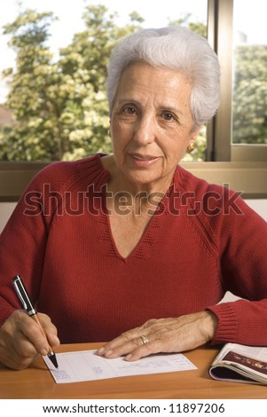 Portrait of a senior lady writing at home - stock photo