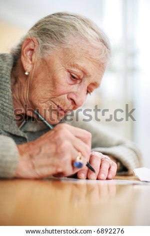 Portrait of a senior lady writing. Close-up, shallow DOF. - stock photo