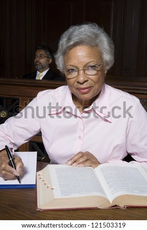 Portrait of a senior lawyer writing notes with man in the background
