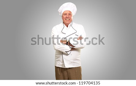 Portrait Of A Senior Male Chef On Gray Background - stock photo