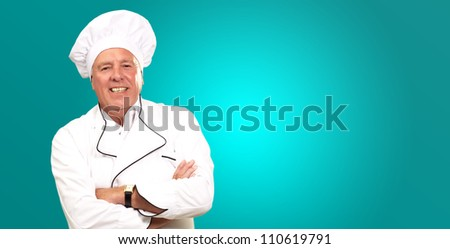 Portrait Of A Senior Male Chef On turquoise Background - stock photo