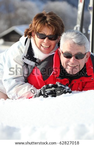 Portrait of a senior man and a senior woman laid in snow