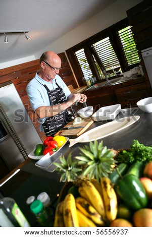 Portrait of a senior man cooking - stock photo