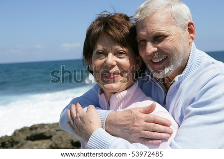 Portrait of a senior man embracing a senior woman in front of the sea - stock photo