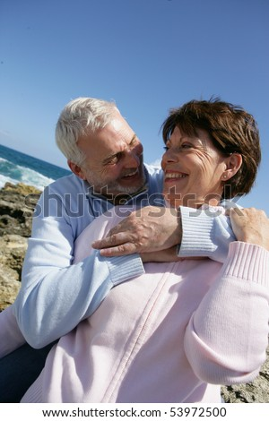 Portrait of a senior man embracing a senior woman in front of the sea