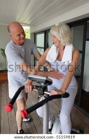 Portrait of a senior man helping a senior woman in making exercise bike - stock photo
