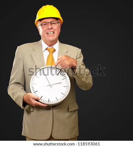 Portrait Of A Senior Man Holding A Wall Watch On Black Background - stock photo