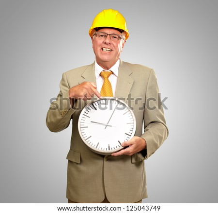 Portrait Of A Senior Man Holding A Wall Watch On Gray Background - stock photo
