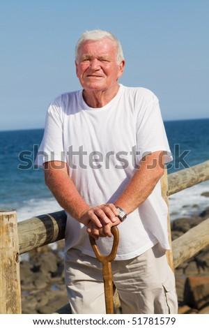 portrait of a senior man holding cane on beach - stock photo