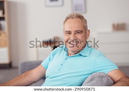 Portrait of a Senior Man in Casual Sky Blue Polo Shirt, Relaxing at the Couch and Smiling at Camera in Close up - stock photo