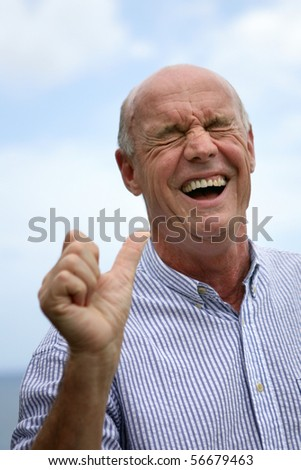 Portrait of a senior man laughing - stock photo