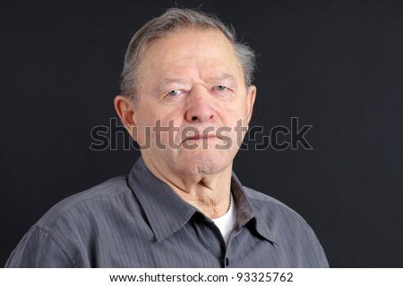 Portrait of a senior man looking very serious, sad or depressed looking at camera with blue eyes, great details, shot in studio over black. - stock photo