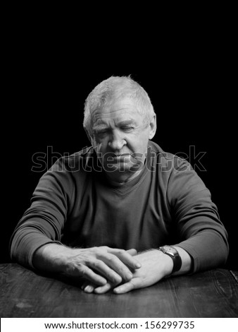 Portrait of a senior man looking very serious, sad or depressed ,studio shot over black.  - stock photo