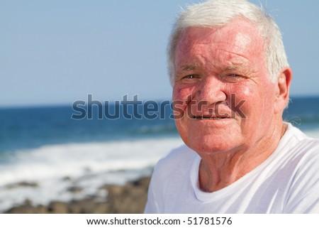 portrait of a senior man on beach - stock photo