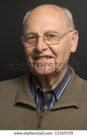 Portrait of a senior man on dark background - stock photo