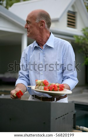 Portrait of a senior man preparing fish skewers on a plancha - stock photo