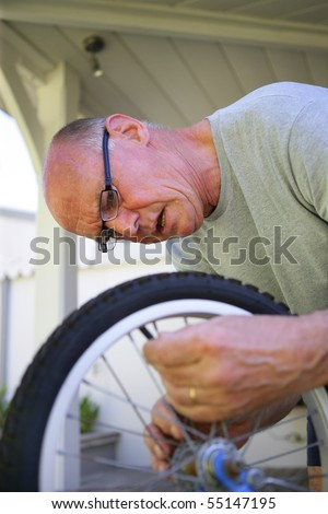 Portrait of a senior man repairing a kid bike