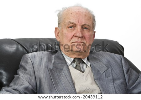 Portrait of a senior man sitting in an armchair isolated against a white background. - stock photo