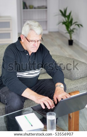 Portrait of a senior man sitting in front of a laptop computer - stock photo