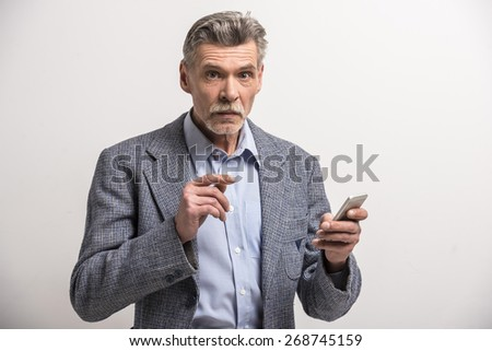 Portrait of a senior man using phone and looking at camera.